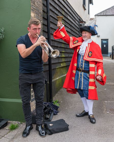 A musician playing trumpet watched by Town Crier Richard Harris, Great Dunmow, Essex