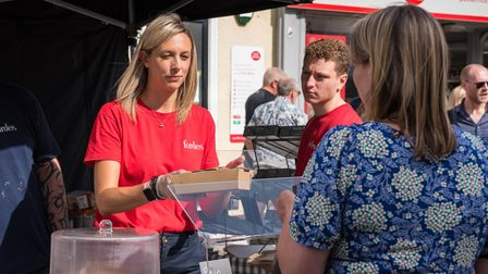 A woman buying some tasty looking food at Great Dunmow's Summer Market, Essex