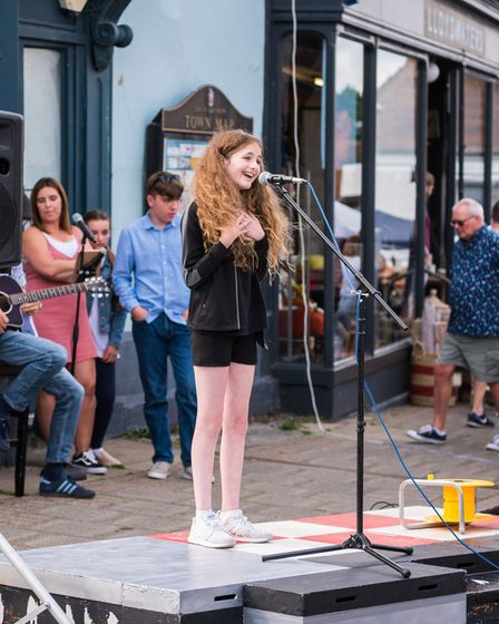A young woman with a microphone, performing at Great Dunmow's Summer Market, Essex