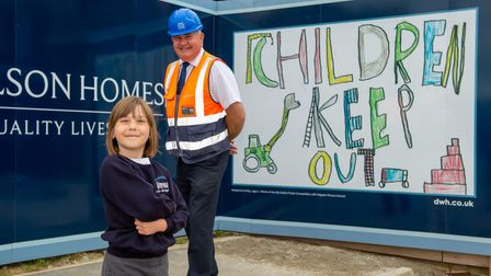 Ruby and site manager Andy Barker with Ruby's winning site safety banner at Marham Park in Bury St Edmunds