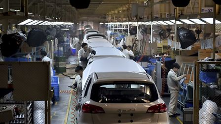 In this photo taken Monday Jan. 18, 2016, Chinese workers labor on the assembly line of the X5 SUV o