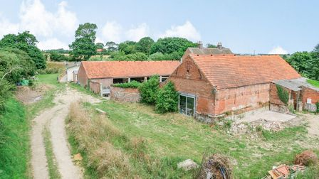 Brick-built 18th century Norfolk barn with single-track driveway and grass and shrubland around it