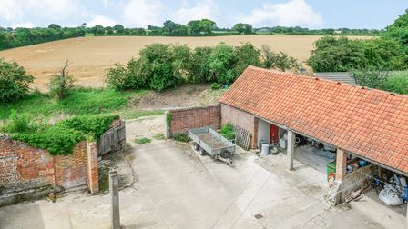 Aerial view of six-bay cart shed overlooking courtyard and surrounded by open Norfolk fields