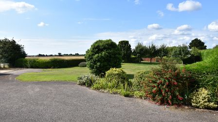 Large landscaped gardens, tarmac driveway and field views across Suffolk countryside