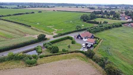 Aerial view of bungalow with large driveway, separate garage surrounded by flat Suffolk countryside