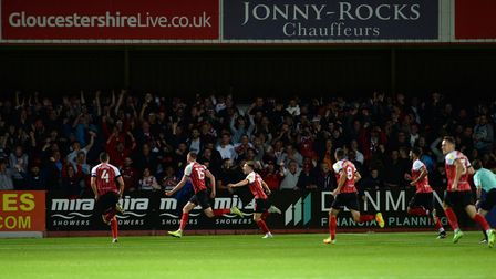 Home players celebrate after scoring the winning goal at Cheltenham Town.