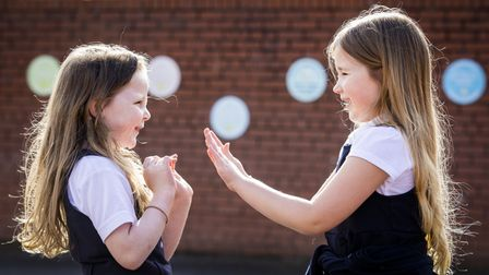 File photo dated 08/03/21 of children Scarlett Greggan (left) and Madison Lowry playing patty cake d