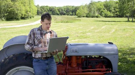 Farmer with tractor and laptop computer