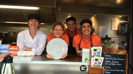 Justina and helpers in their burger van. She is holding their food award