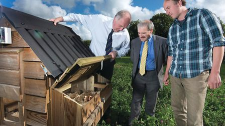 Tom, right, shows visitors one of his hen houses