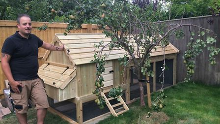 Dan Cherry with his Acres Cottage with shiplap roof, under a pear tree