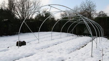 A polytunnel frame in place and ready to receive cladding after trench is dug Credit: Charles Dowdi