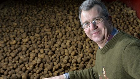 Farmer Tim Papworth pictured with potatoes grown at his farm in Felmingham. Picture by Adam Fradgle