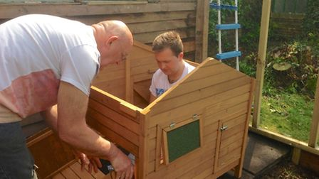 Tom and his dad Robert assemble a coop
