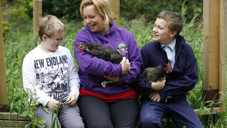 Teacher Debbie Isley with two of the students and chickens