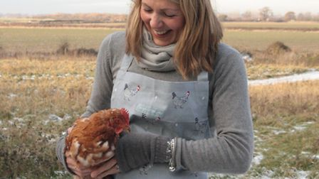 Sophie Allport wearing a chicken design apron. INSET: A Sophie Allport coaster, placemat and napkin