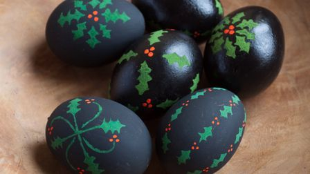 Hand-painted holly patterns really stand out on a dark background
