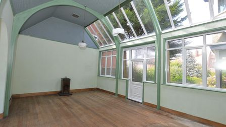 Artists studio with timber ceiling, green arched beams, wood flooring and lots of windows