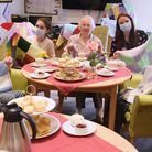 Some of the residents of the Beeches Care Home at East Harling enjoying a tea party as they knit squ