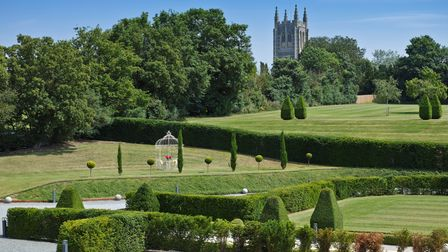 View over well-tended gardens in the Suffolk countryside with a medieval church in the distance