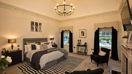Large master bedroom suite with two sash windows, black curtains and striped rug on lush grey carpet