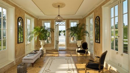 Huge grand villa-style reception hall with marble tiled floor, plants and bright and light windows