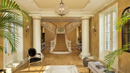 Mediterranean style reception hall with huge sweeping staircase, marble floors and hanging glass chandelier