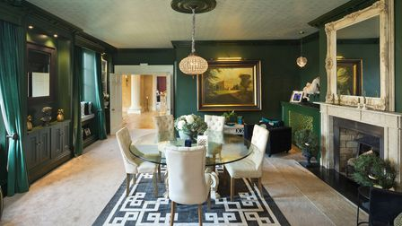 Dining room with dark green walls, lush white carpets, glass-topped dining table with five white chairs opposite a fireplace