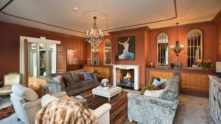Cosy drawing room with two sofas, a roaring fire set into a stone fireplace and doors open into the hall