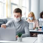 Coronavirus quarantine and office work with colleagues keeping social distancing. Portrait of young