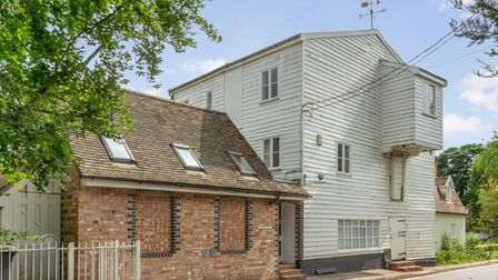 Former water mill with brick extension and white weather board cladding in a leafy setting in Suffolk