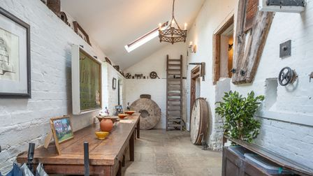 Room in a converted water mill featuring white washed brick walls, timber beams and a skylight