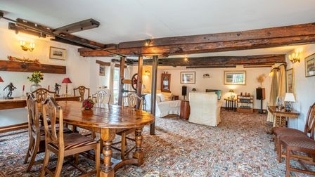 Open-plan dining space with huge timber ceiling beams, patterned carpet and low light wall sconces