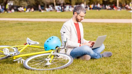 Professional man working on his laptop in a park with his bike on the grass next to him