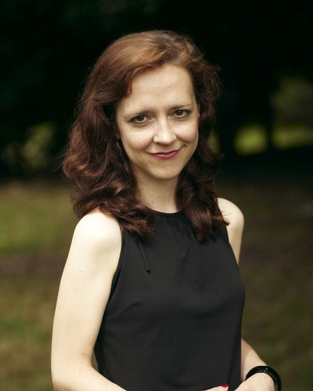 Photo of Megan Abbott, a US crime writer, dressed in black and smiling at the camera