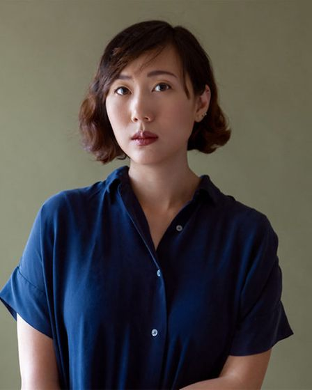 Photograph of Steph Cha, an author, who is staring at the camera, unsmiling, in a blue shirt