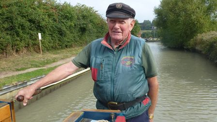 Norman Woolley at the helm of his narrowboat on a canal