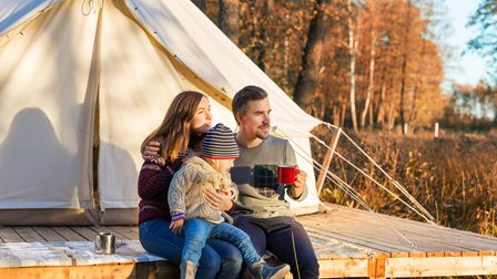 Happy family drinking coffee while sitting near canvas bell tent in the morning in a forest
