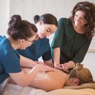 Jennifer Young (right) demonstrates massage techniques to therapists.