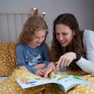 An adult and child reading a book together