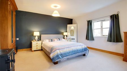 Large double bedroom with blue painted wall, wood-burner, wooden wardrobe
