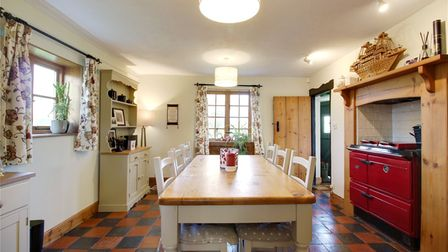 Country-style kitchen with pine dining table, bright red Range cooker and black and terracotta tiled floor