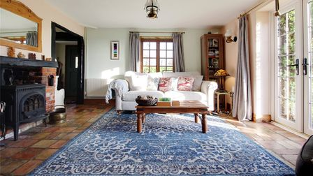 Large sitting room with white sofa, huge blue paisley rug on tiled floor and cast iron woodburner opposite patio doors