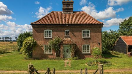 Pretty brick-built period property with tiled roof, central chimney and climbing roses by the front door surrounded by fields