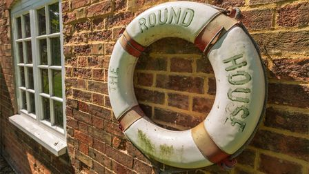 White and red life float hanging on brick wall of house spelling out 'The Round House'
