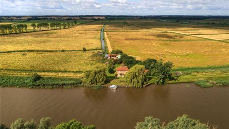 Aerial view of a pretty brick-built period home on the river surrounded by fields