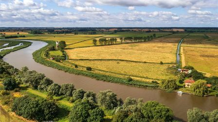 Aerial view of tiny brick-built house on the River Yare, Norfolk, surrounded by yellow fields