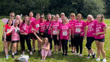 A group of 18 Tesco staff members wearing pink Race for Life tops in Chelmsford