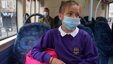 School pupil wearing a face mask on bus.