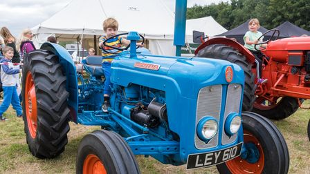 A little boy sits on a blue vintage tractor in Easton, Essex. Behind him, a little girl sits on a red tractor.